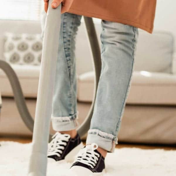 woman in black converse shoes vacuuming living room shag rug