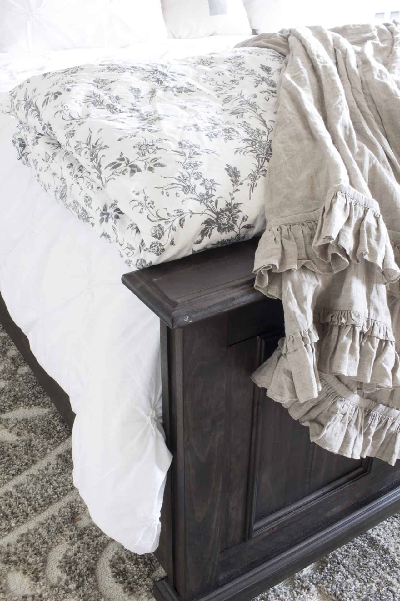 layered neutral and white bedding on rustic king bed