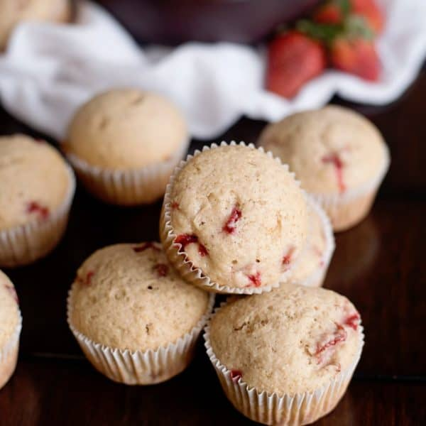 strawberry muffins on the counter with strawberries in background