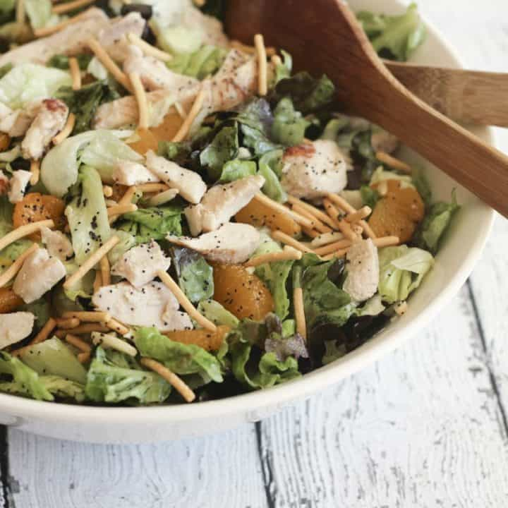 mandarin chicken salad in a white bowl with wooden spoons