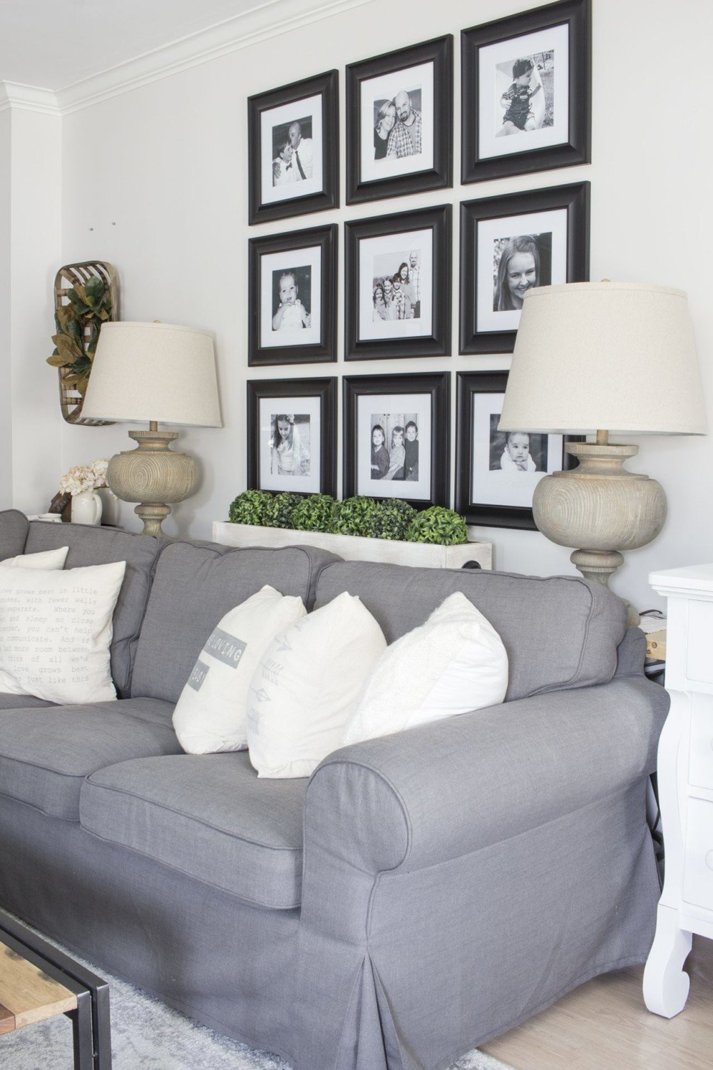 black and white grid gallery wall behind sectional couch to illustrate extra large wall art idea