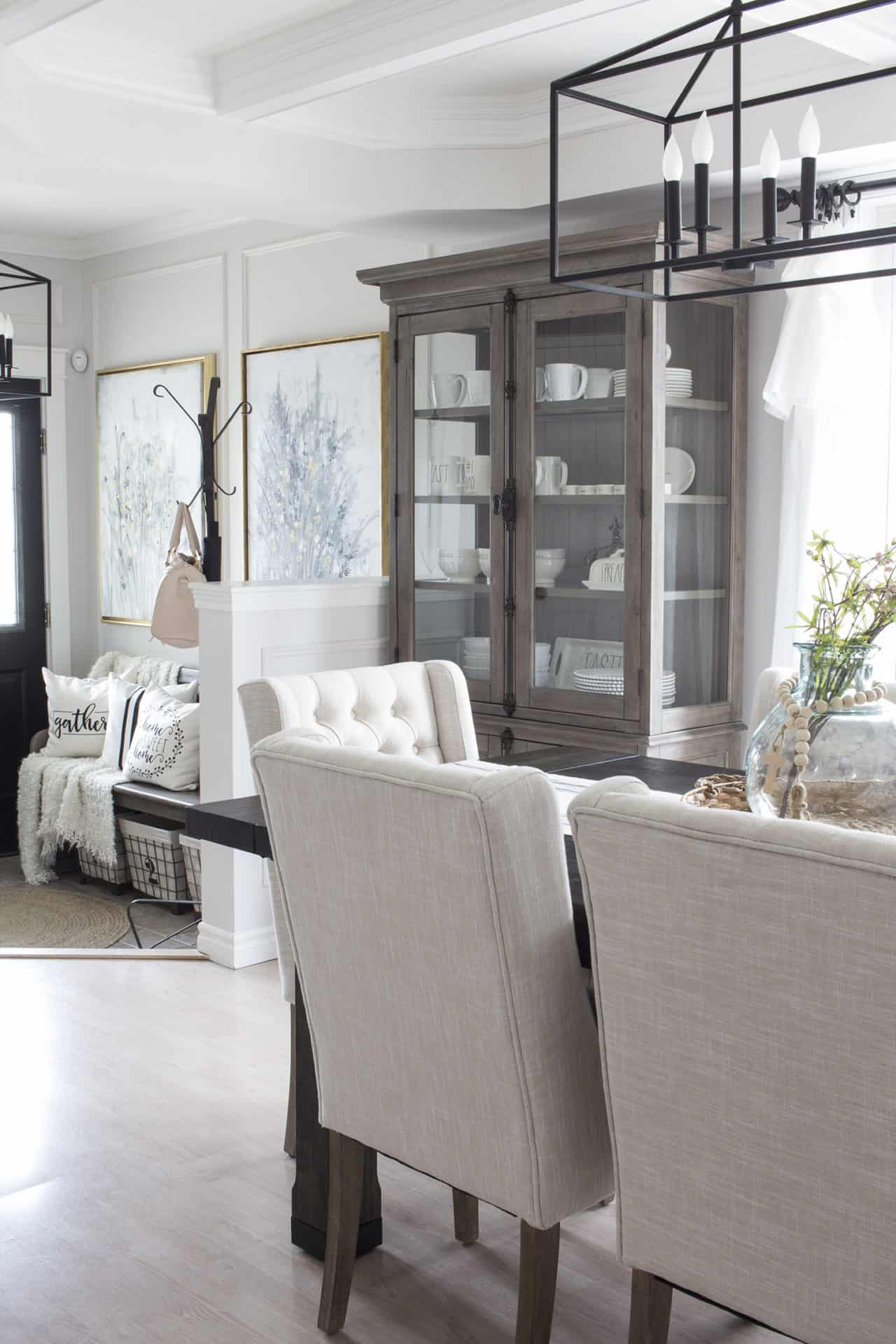 neutral dining room with upholstered chairs and shades of white and taupe to illustrate a good color scheme