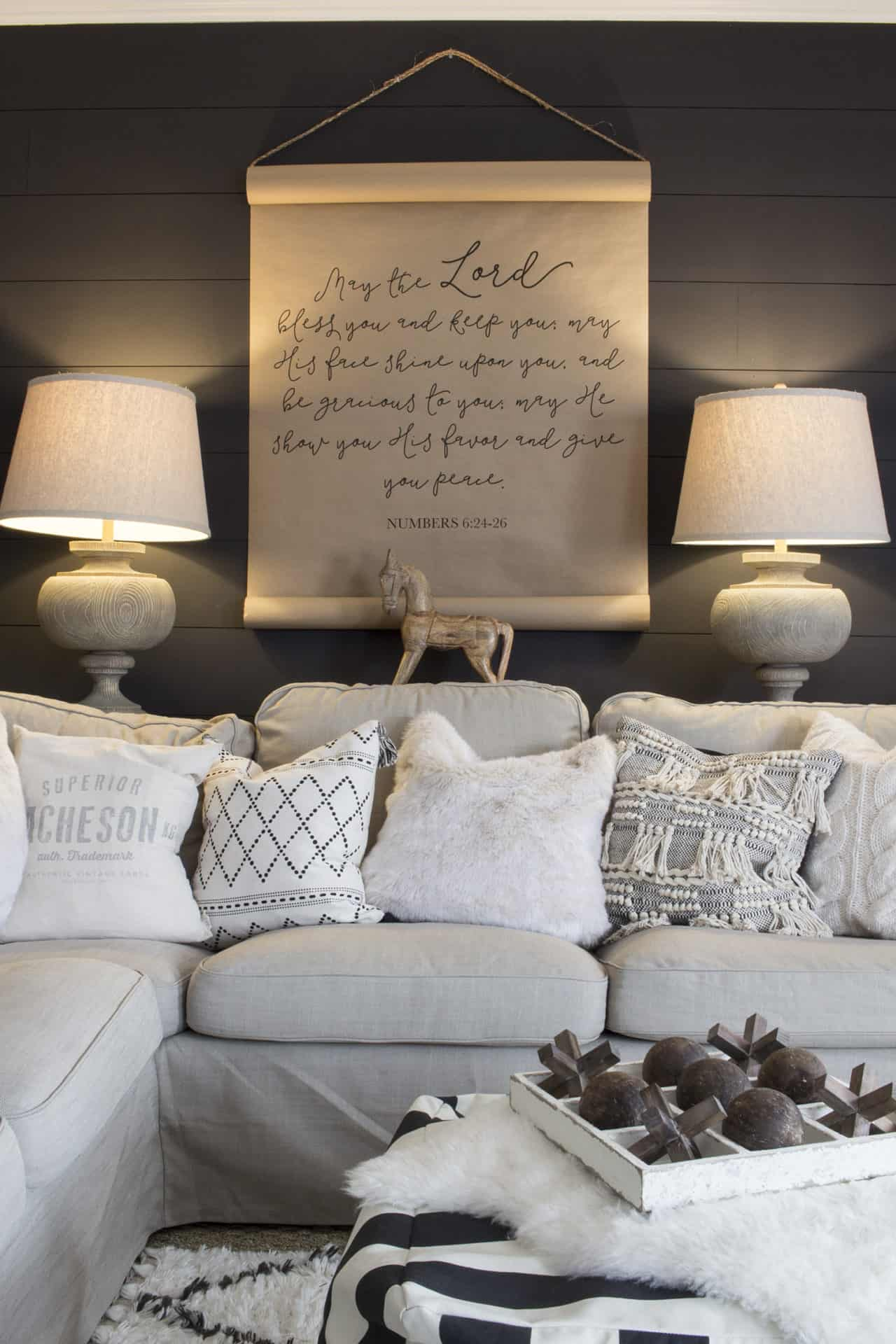 black shiplapped wall with brown kraft paper sign hanging over a cream couch with throw pillows