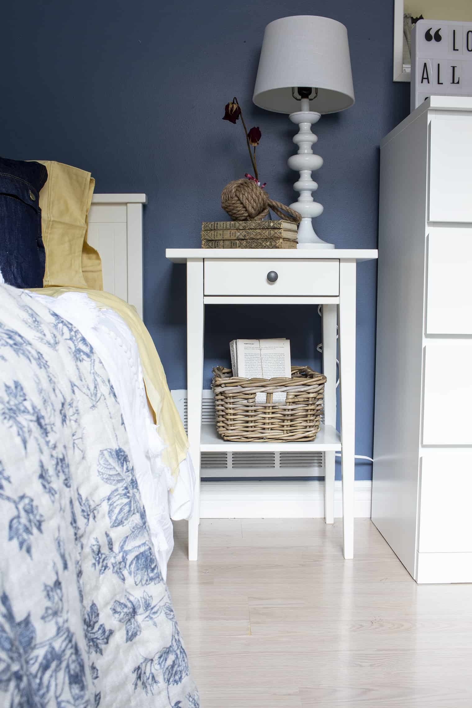 white bedroom nightstand with blue walls and yellow sheets to illustrate the 60-30-10 rule