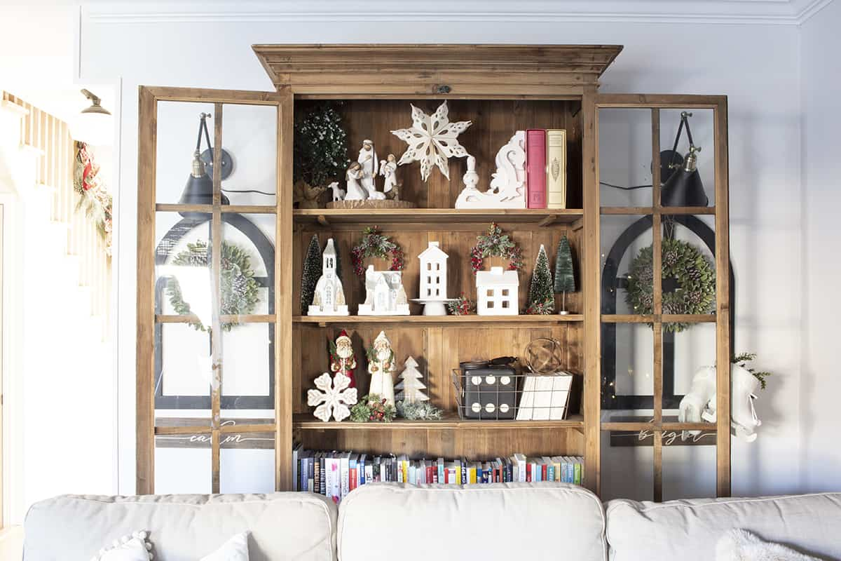 nativity and white ceramic houses in bookcase