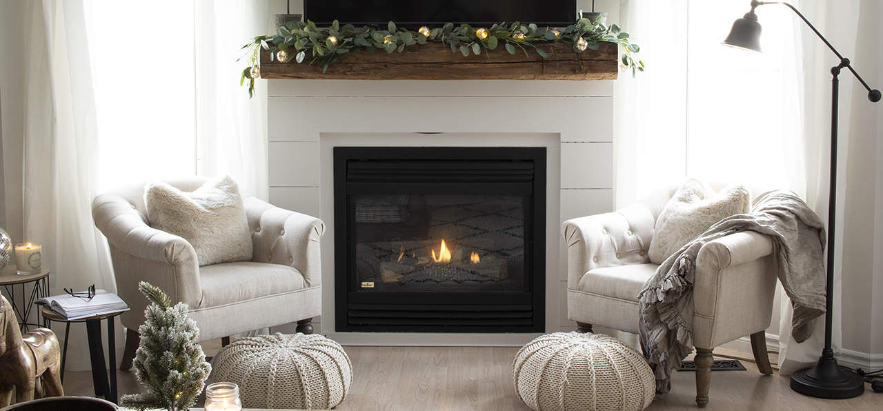 a white shiplapped fireplace mantel with two cozy chairs and footstools, illustrating a neutral home color scheme