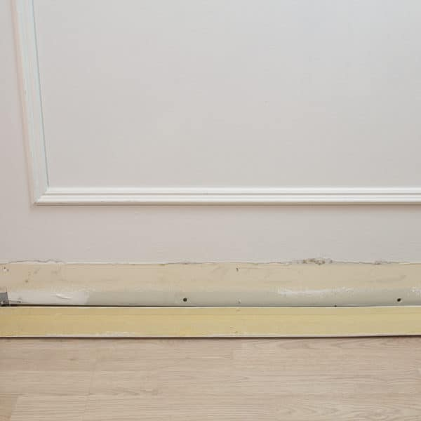 clean baseboard laying on floor beside wall