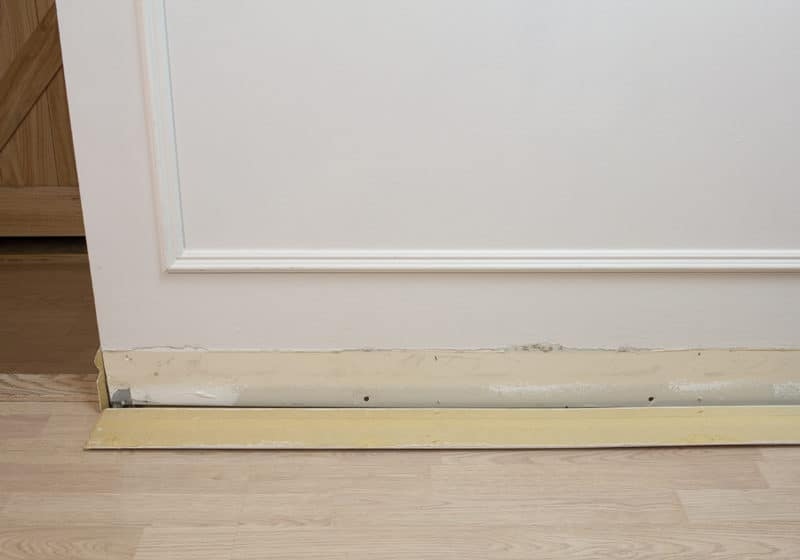 clean baseboard laying on floor beside wall