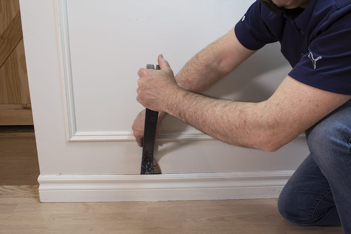 a man using a putty knife and pry bar to carefully detach baseboard from the wall