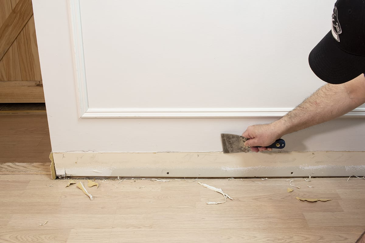 a man using a putty knife to scrape off remaining caulking
