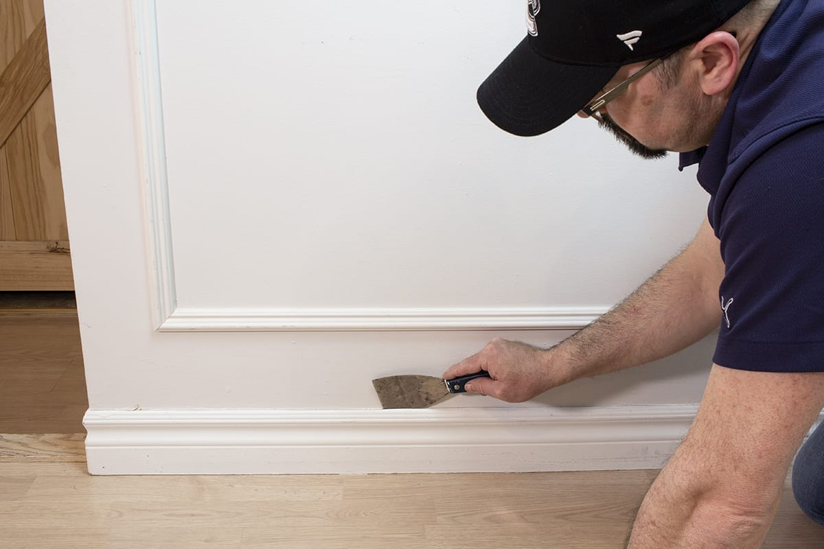 a man sliding a putty knife behind baseboards to detach them from the wall
