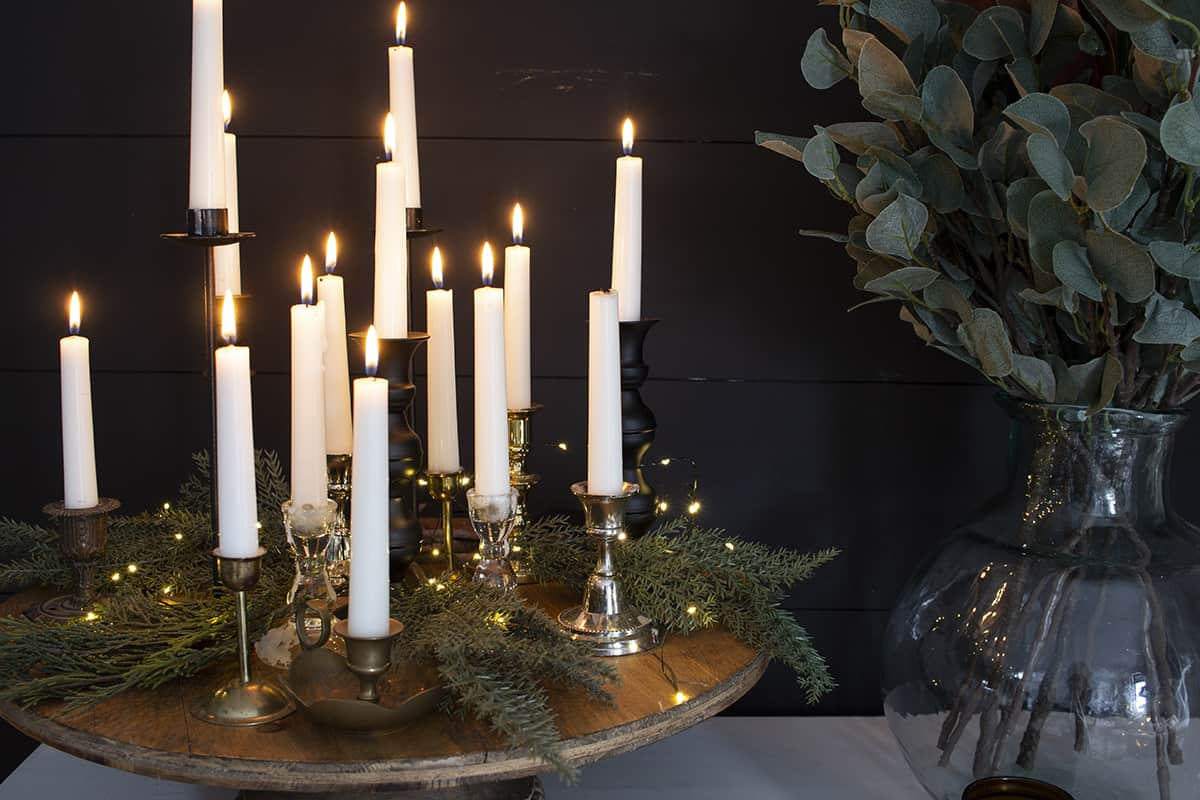 thrifted candlesticks on cake stand with twinkle lights and greenery