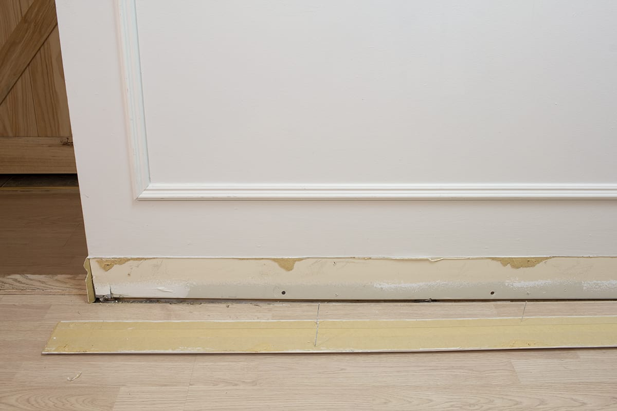 baseboard with nails still intact shown removed from the wall