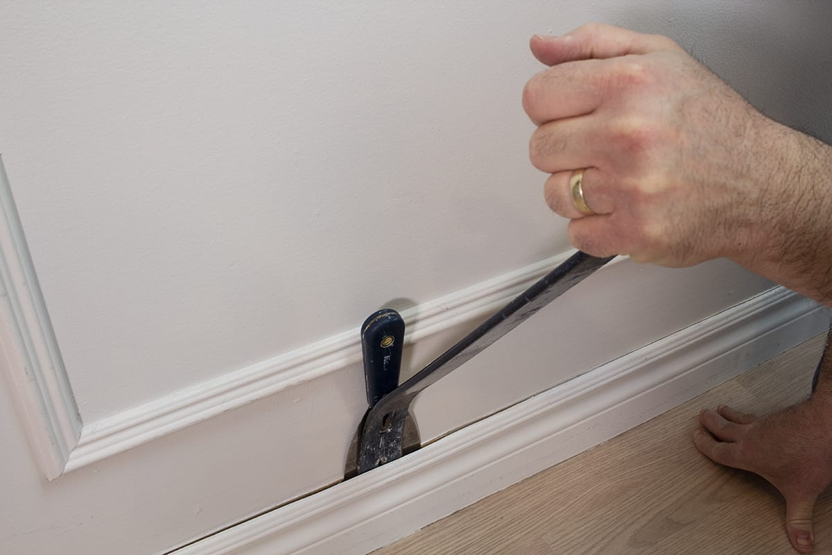 a man using pry bar to remove trim without damage