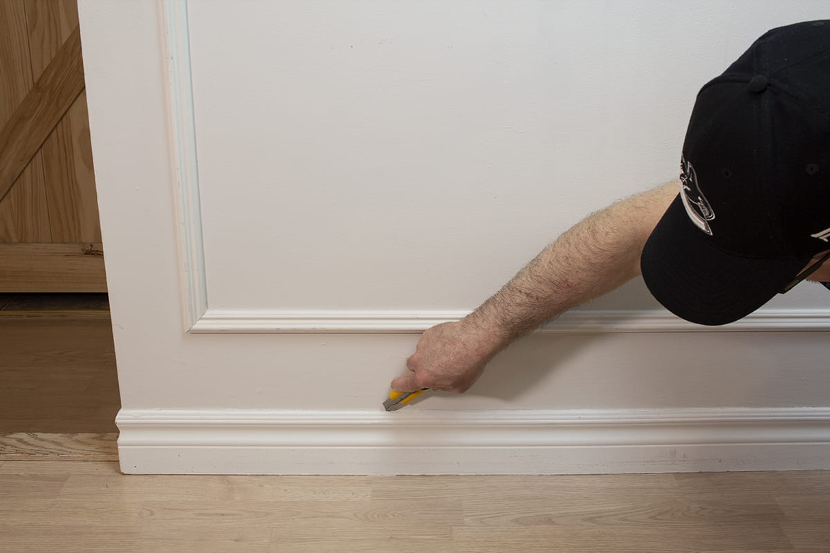 man using a utility knife to cut into caulking on top of baseboard