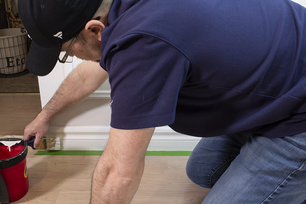 man painting baseboard trim