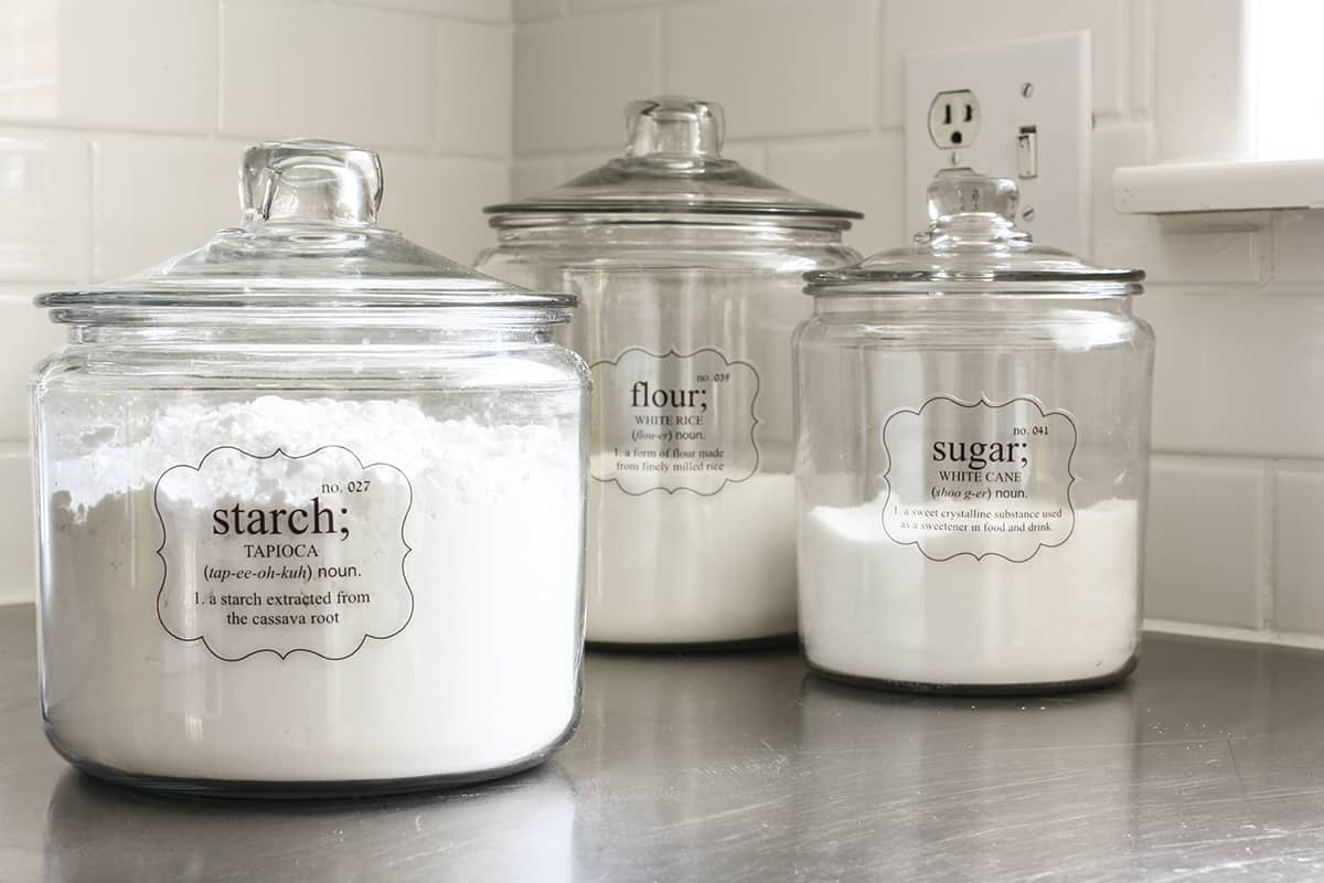 anchor hocking jars with clear pantry labels on steel counter
