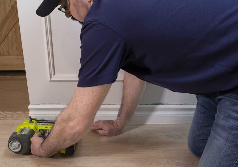 man brad nailing baseboard in place