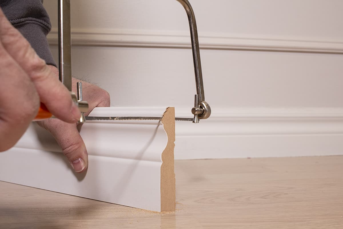 man cutting into the baseboard with the coping saw