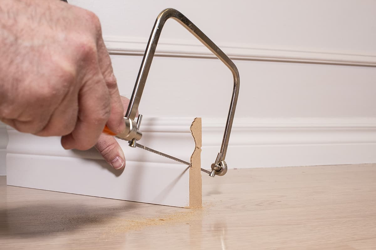man cutting further down the baseboard profile with a coping saw