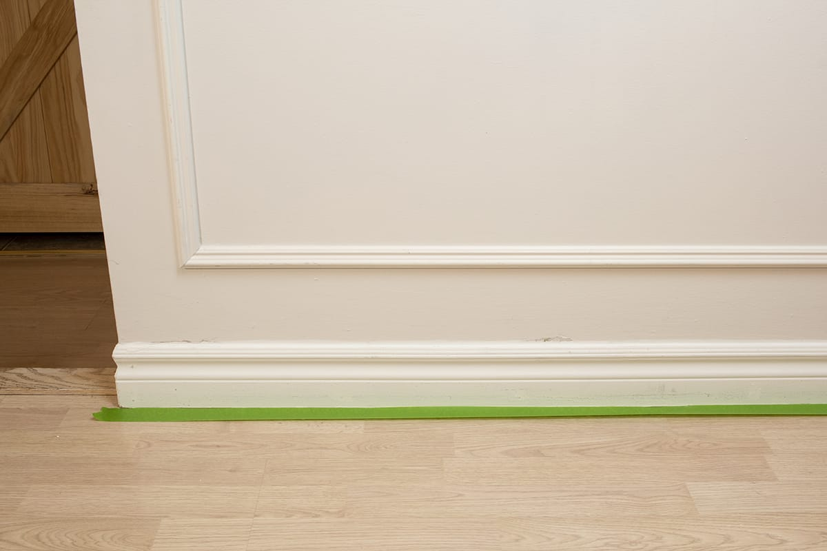 green painters tape on floor tucked under baseboard