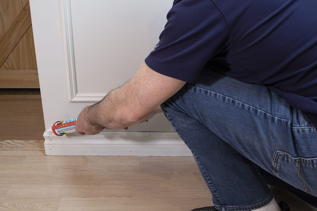 man caulking baseboards