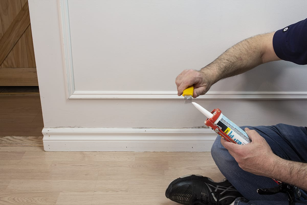 man demonstrating how to cut off top of caulking tube