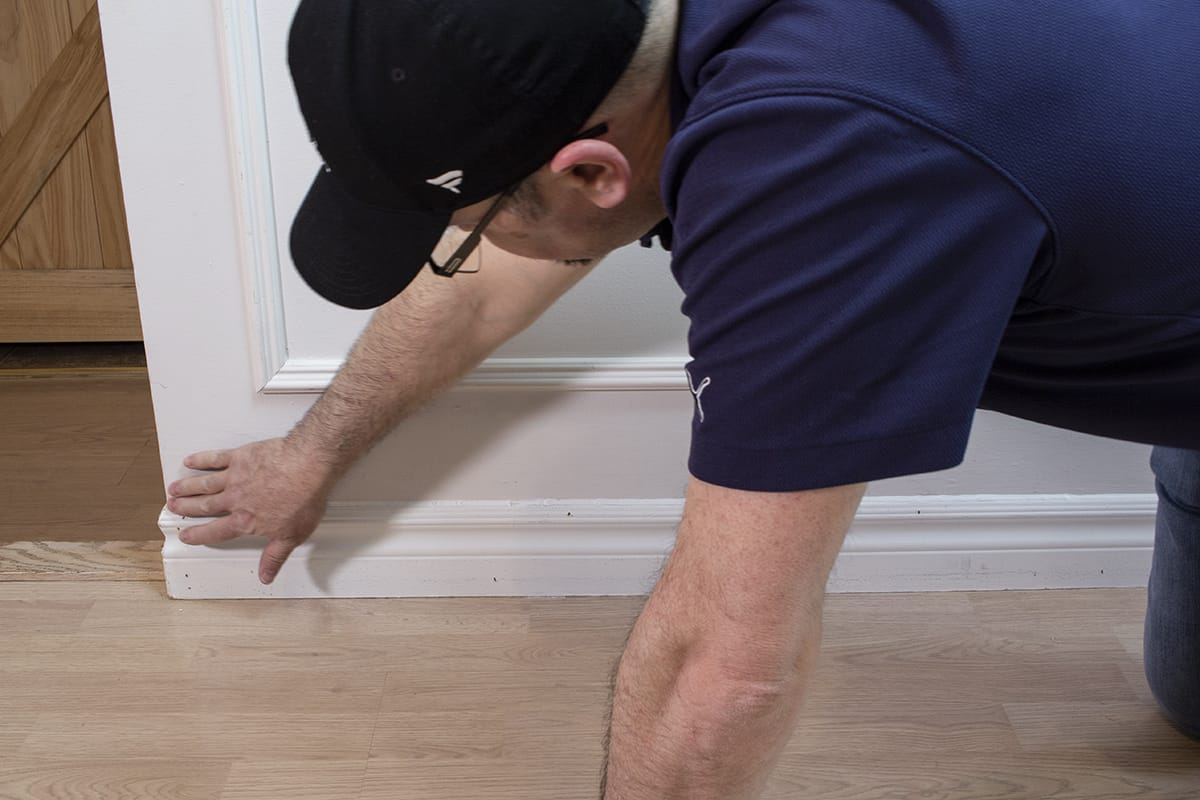 man using middle finger to smooth caulking against baseboard and wall