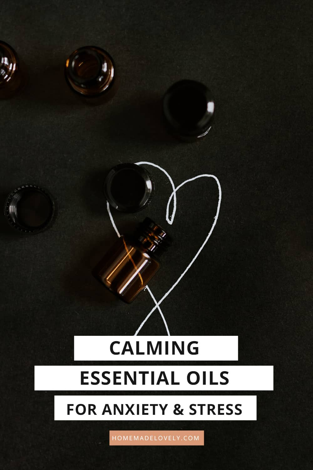essential oil bottles on black background with white drawn heart