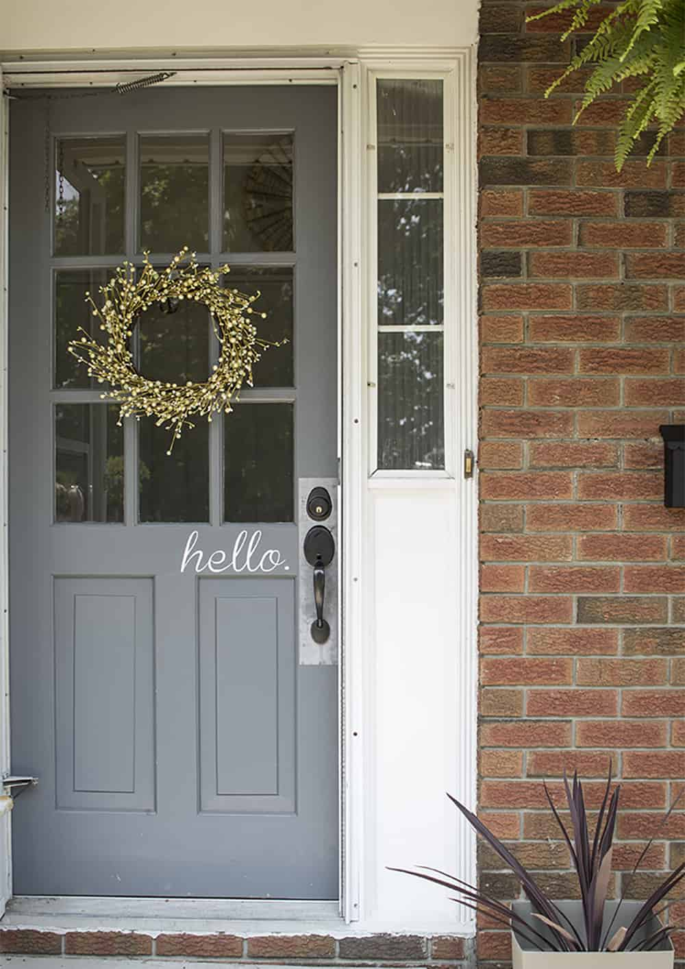 gray door with green berry wreath welcoming porch