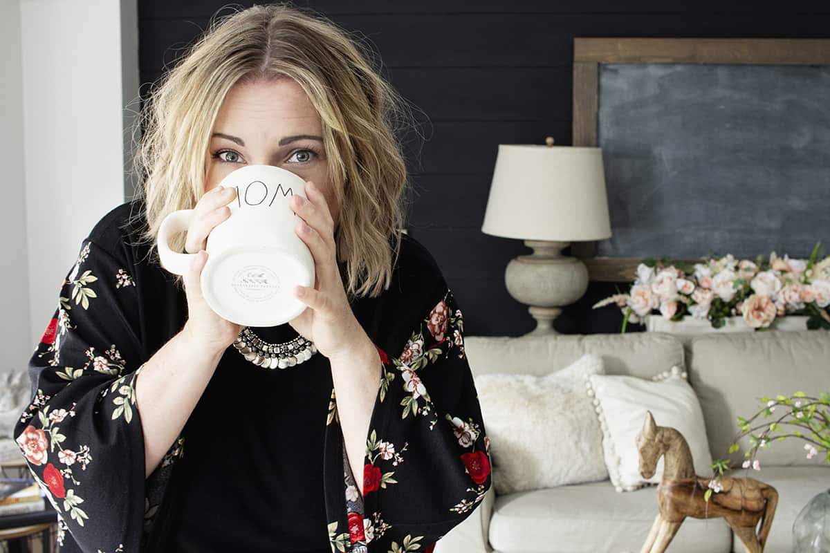 shannon sipping from a MOM mug in a blouse with black shiplap background