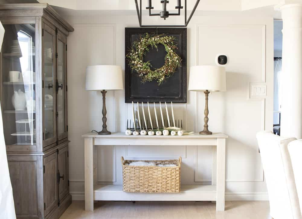 dining room sideboard with plates and chalkboard with wreath