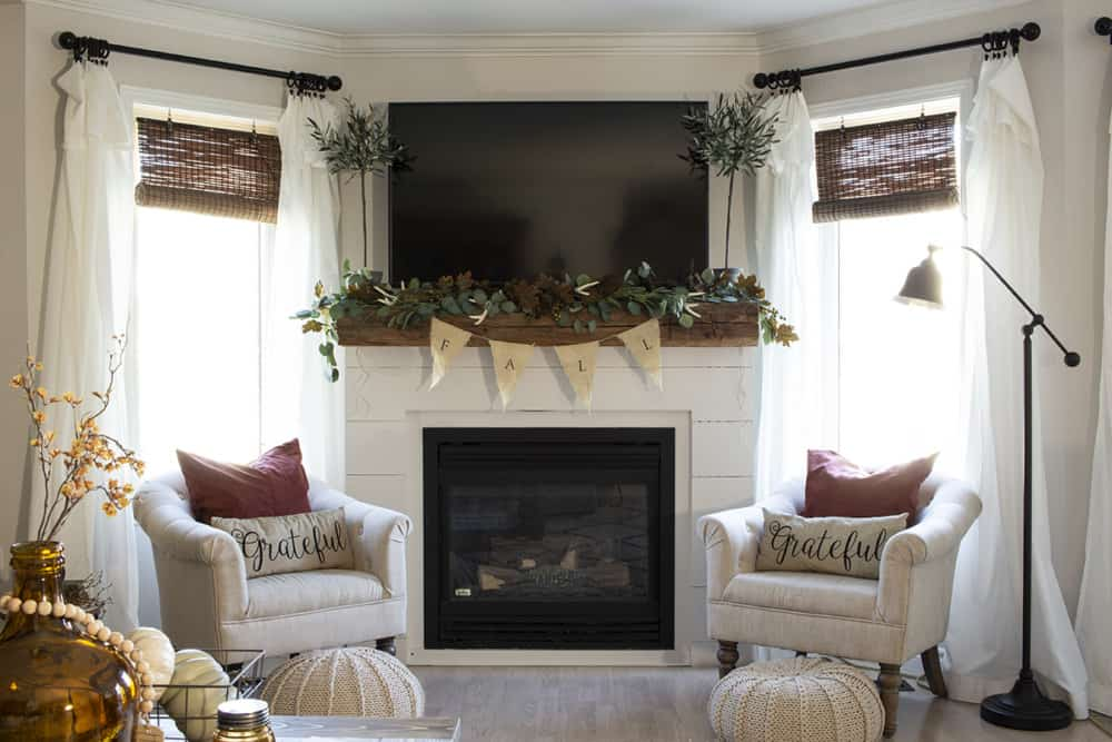 living room fireplace with tv off and rust pillows