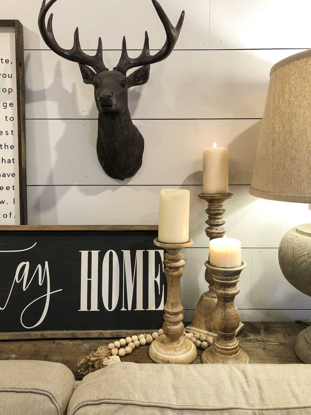 Candles on sofa table stag head on white shiplap wall