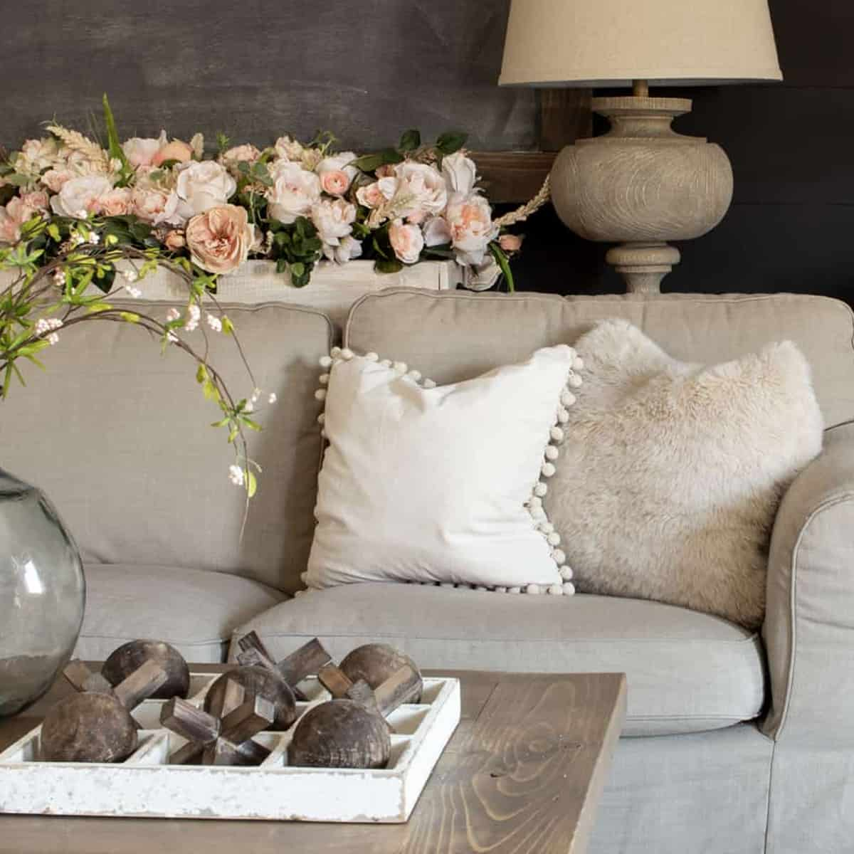 taupe couch with cream pillows, pink flowers behind on sofa table with lamp