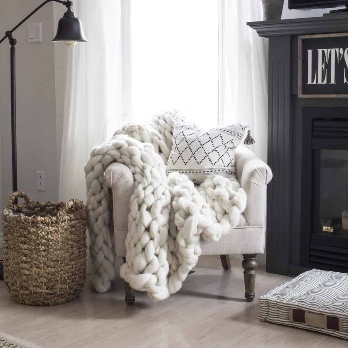 farmhouse style chair with a chunky knit blanket, basket and lamp beside a grey fireplace