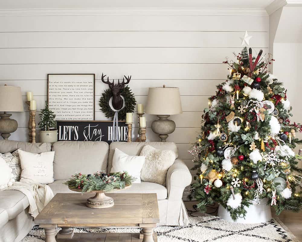 white shiplap wall, beige ikea sofa, christmas tree all decorated