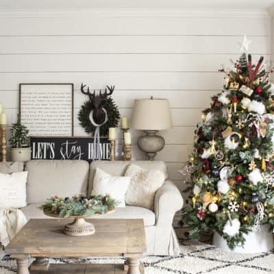 white shiplap wall, beige ikea sofa, christmas tree all decorated