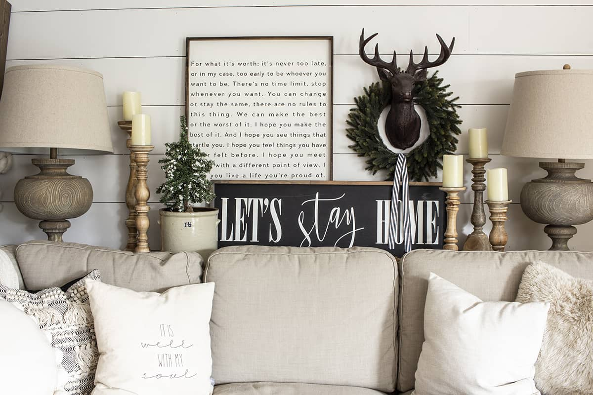farmhouse signs on sofa table deer head over beige sofa