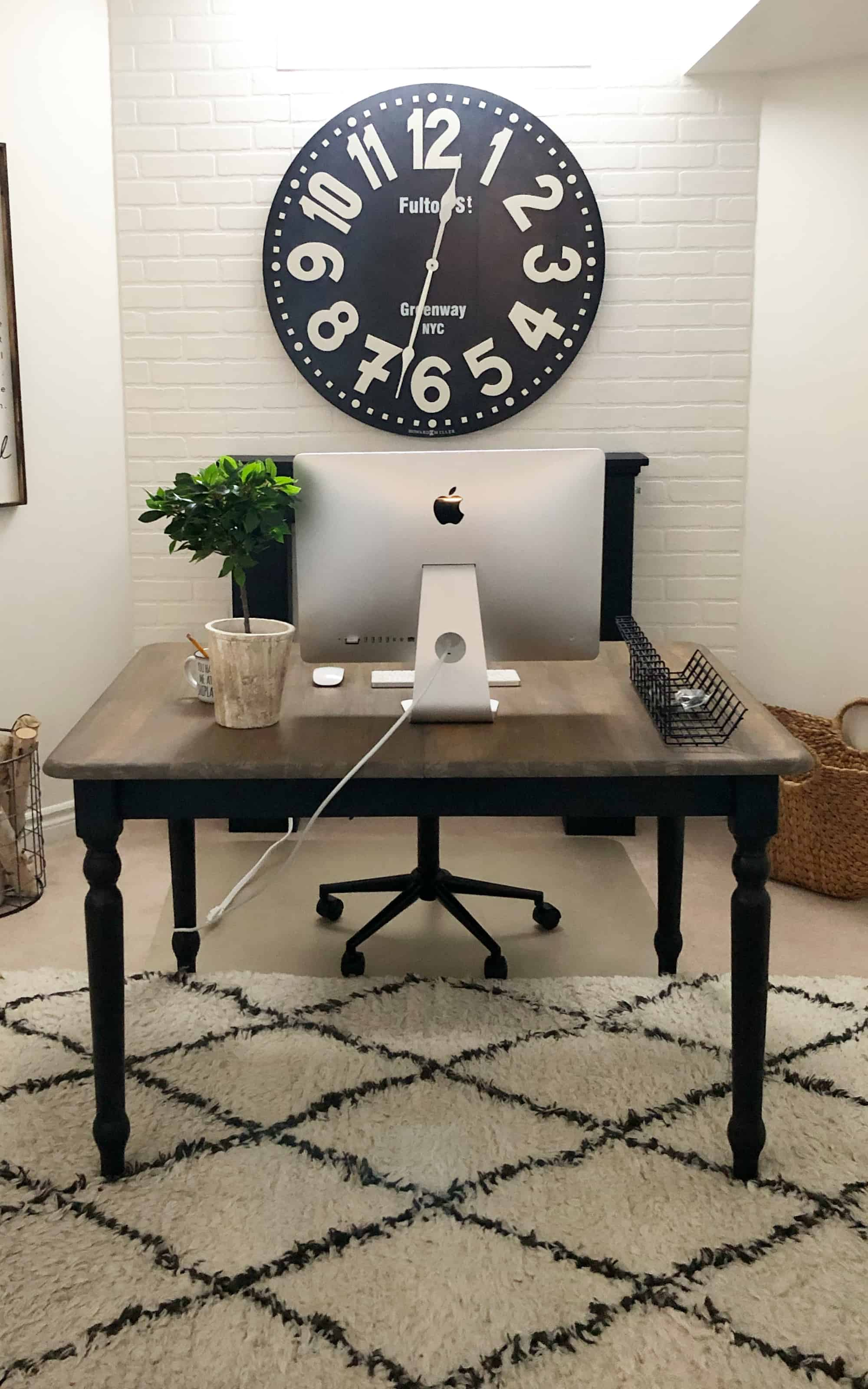 home office with trellis rug, mac on table desk and large black wall clock