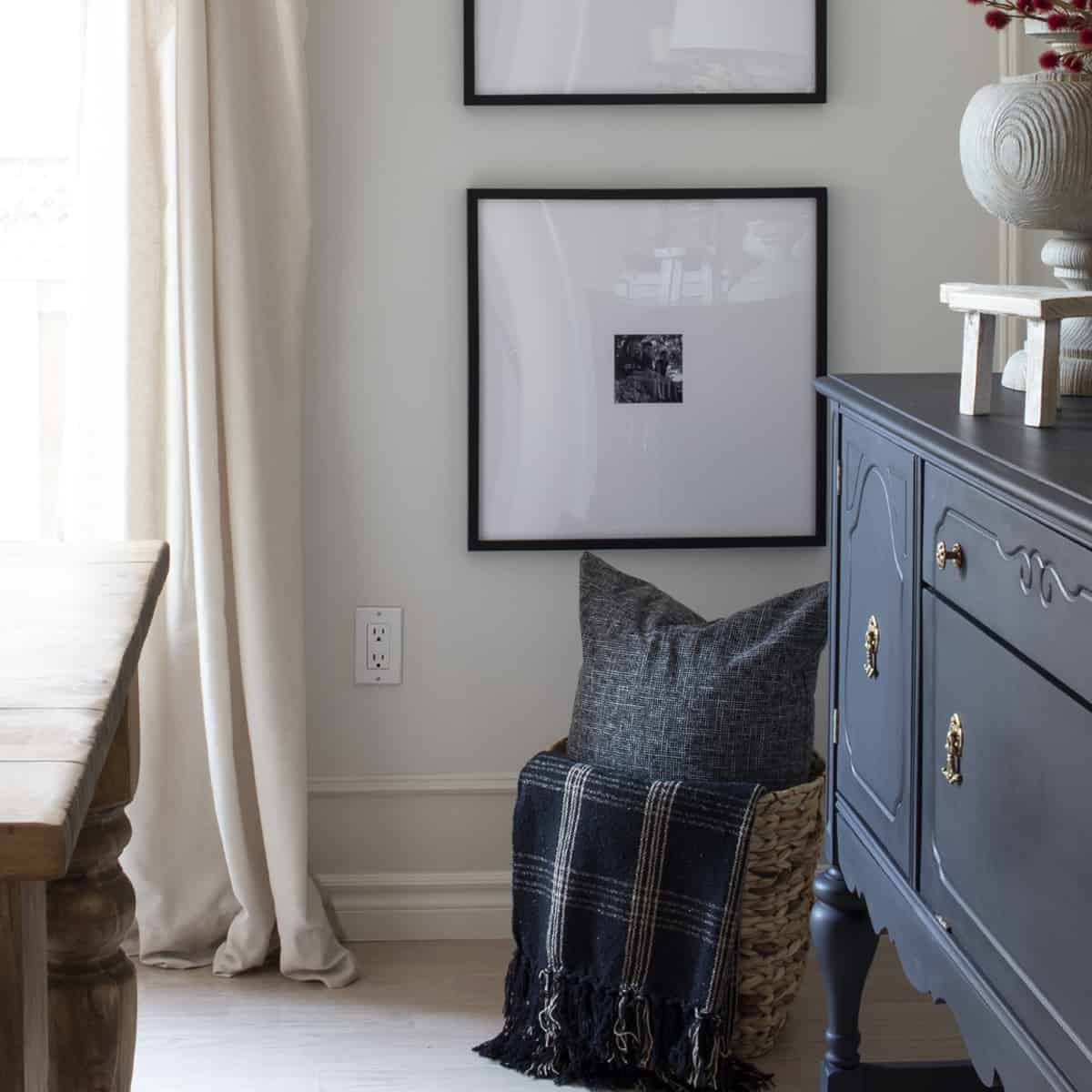 black buffet and farmhouse table in front of framed family photos