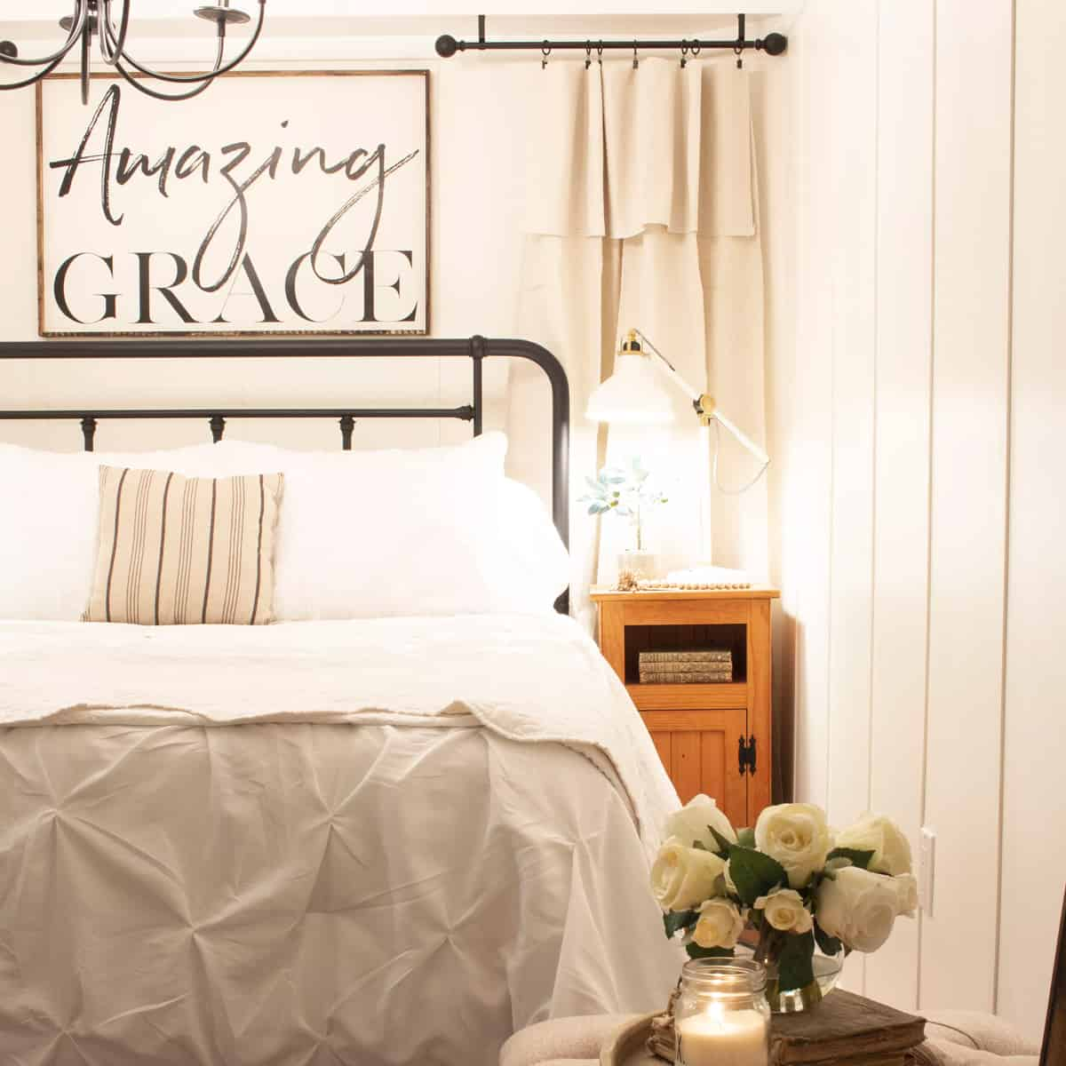 basement guest room with white board and batten walls, white bedding and amazing grace script sign over iron bed frame