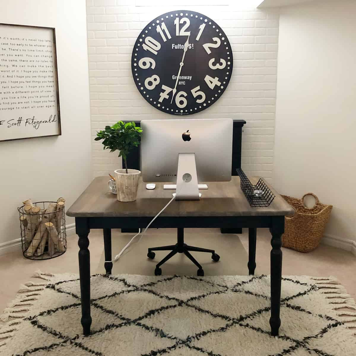 basement office with white walls, trellis rug and mac on farmhouse table style desk