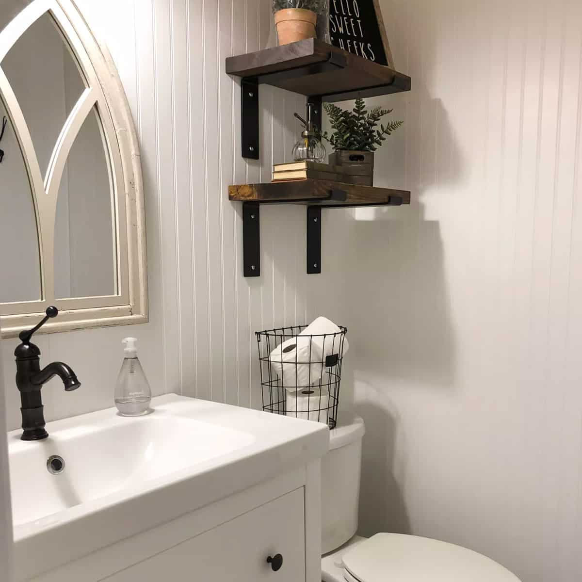 powder room with white beadboard walls, arched gothic mirror and open shelves