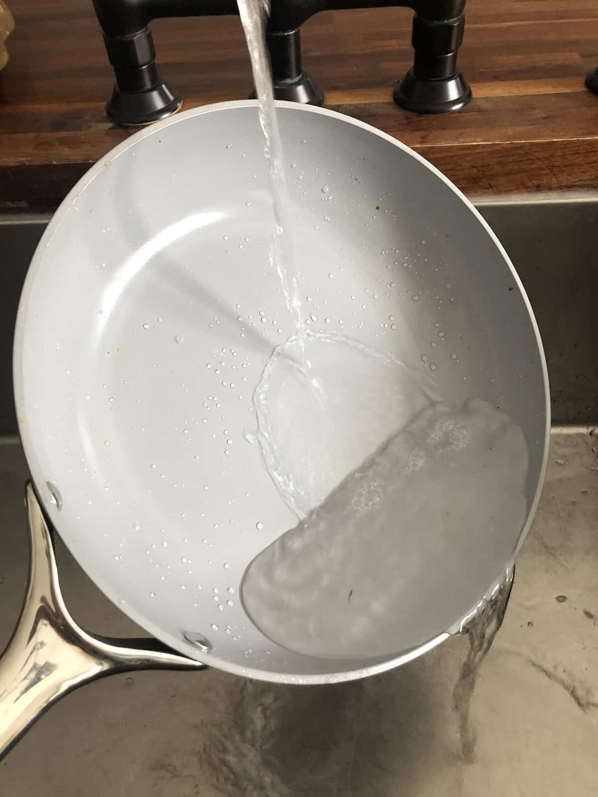 rinsing a Caraway home non-stick frypan in the sink