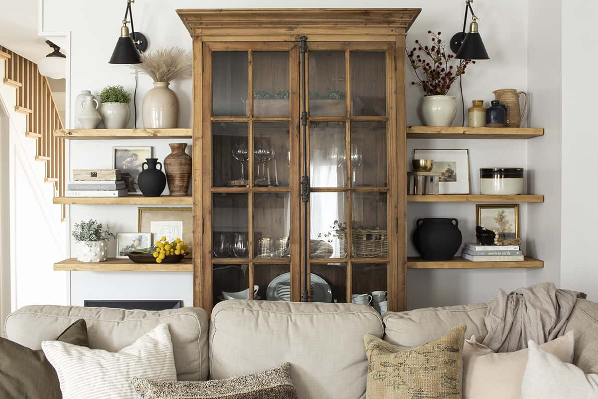 Floating shelves on either side of pine glass door cabinet