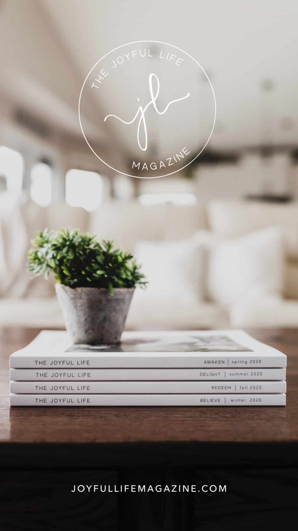 Joyful Life Magazine stacked on wood coffee table with white couch behind