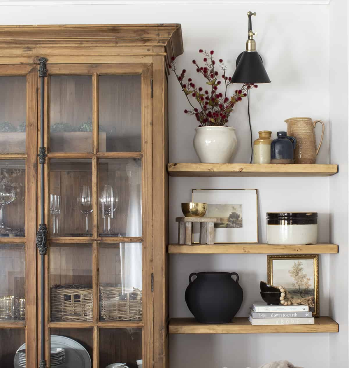 Pottery books and gold frames on floating shelves