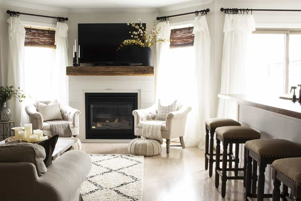 TV over shiplap and barn beam fireplace mantel