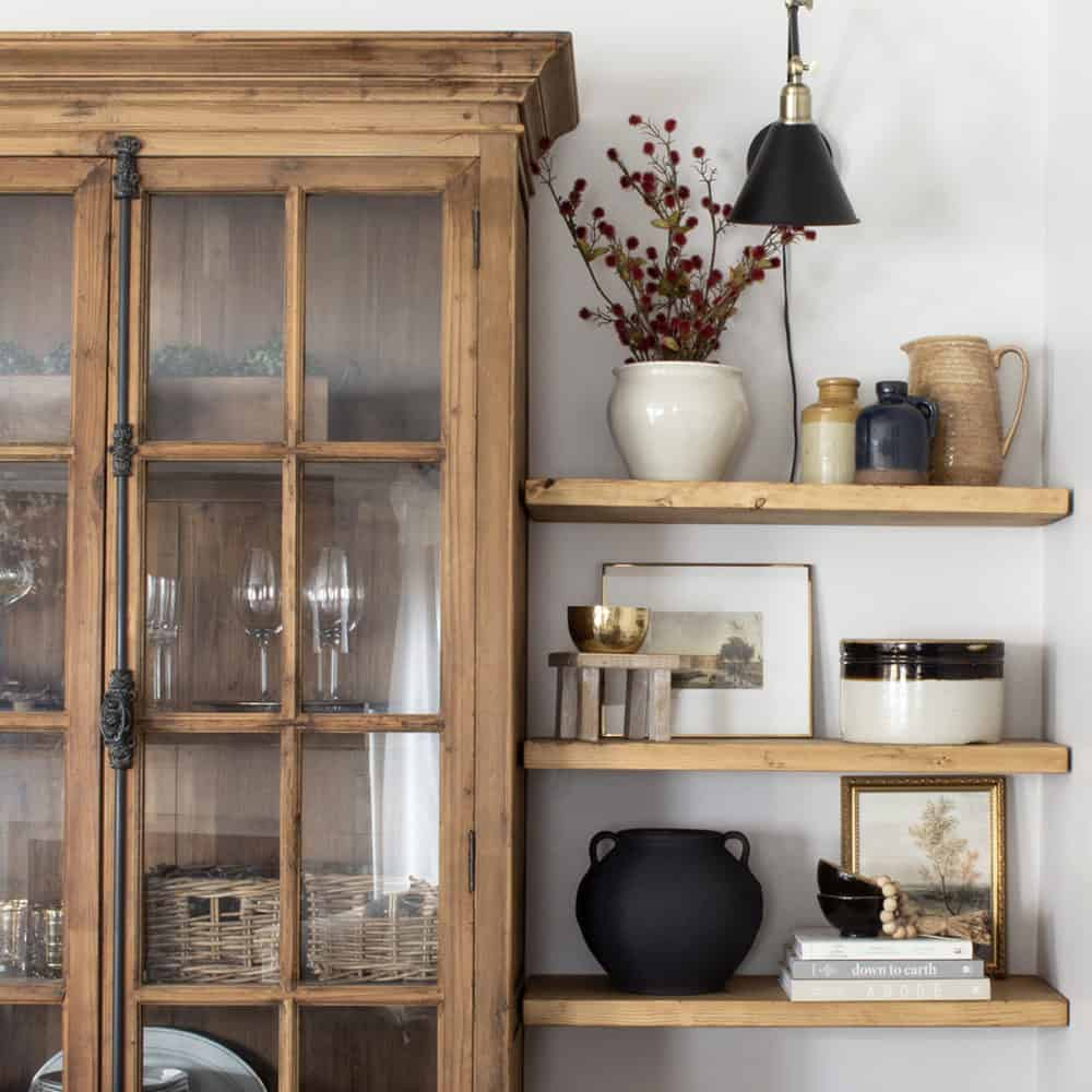 pine bookcase with glass doors beside floating shelves with pottery and books